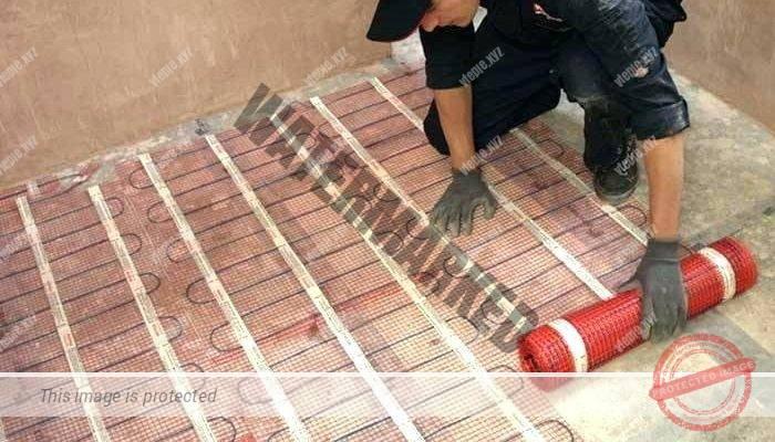 Человек укладывает кабельный мат электрического теплого пола